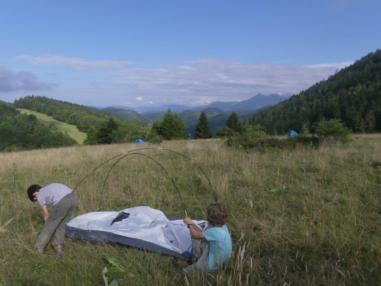 Deux enfants montent une tente en montagne